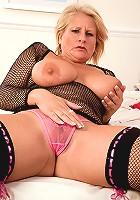 Busty grandma in white stockings toying her hairy muff