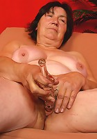 Old chubby slut drills herself with a large dildo