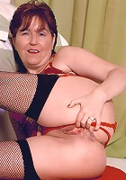 Horny mature model wearing a sexy red lingerie and spreading her moist looking pussy flaps