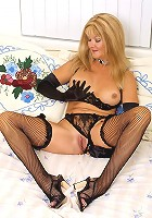 Blonde mature model playing with her huge hooters and sitting on top of a dildo