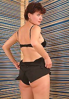 Mature brunette bares it all in front of the camera to show off her fleshy backside