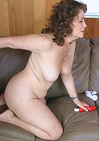 Mature babe naked and sitting in a couch while cramming her pussy slit with a dildo live