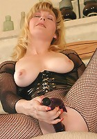 Matured blonde in see-thru BDSM suit playfully posing and toying her sex toys