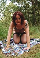 Pretty redhead in her prime years stripping off her clothes in a public park and masturbating