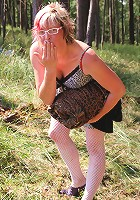 Mature slut playing in an open field with her pussy