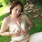 Horny mature slut playing in the garden with her pussy