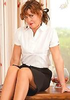 Seductive secretary pulls down her skirt revealing her red panties