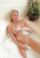Anilos cougar gets wet in the tub and slides a toy in her pussy