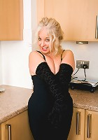 47 year old Caresse hams it up while getting naked in the kitchen