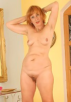 Redheaded Karoline spreads her legs and her hairy pussy