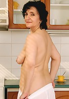 52 year old Sandra D shows off her full bush and tits in her kitchen