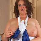 Big and busty Dusty pulls aside her apron and shows big tits