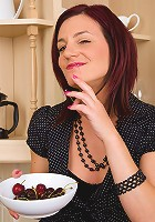 Beautiful redheaded MILF Sofia busy in the kitchen with her cherries