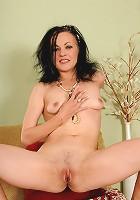 Petite mature brunette Claudia K slips off her slinky black lingerie