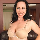 Busty and brunette Kira poses in and out of sexy tight nylons
