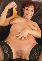 Mature redhead Nika masturbates her very wet pussy.