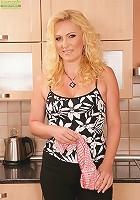 Older blond babe Caroline gets naked in the kitchen.