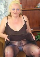 The mature blonde slut in her black pantyhose is getting fucked by a much younger man